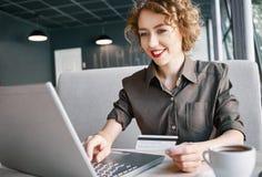 Mujer con el ordenador portátil en café Imagen de archivo