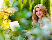 Mujer con el ordenador portátil en el jardín Imagenes de archivo