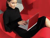 Mujer con el ordenador portátil en el sofá a Fotos de archivo libres de regalías