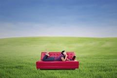 Mujer con el ordenador portátil en el sofá al aire libre Imágenes de archivo libres de regalías