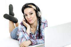 Mujer con el ordenador portátil en la hoja blanca en su cama Imagen de archivo