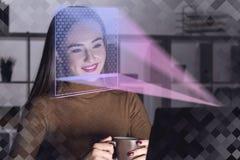 Mujer con el ordenador portátil en la oficina, reconocimiento de cara foto de archivo