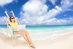 mujer con el ordenador portátil en la playa tropical Imagen de archivo