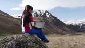 Mujer con el ordenador portátil en las montañas almacen de metraje de vídeo