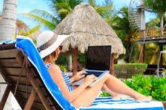Mujer con el ordenador portátil en vacaciones tropicales Imágenes de archivo libres de regalías