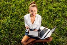 Mujer con el ordenador portátil, la tableta y el teléfono Imagen de archivo
