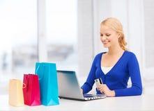 Mujer con el ordenador portátil, los panieres y la tarjeta de crédito Foto de archivo