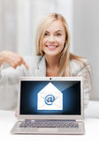 Mujer con el ordenador portátil que señala en la muestra del correo electrónico Imagen de archivo