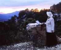 Mujer con el ordenador portátil que se coloca en la cima de la montaña en la puesta del sol Imagen de archivo libre de regalías