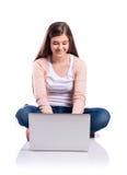 Mujer con el ordenador portátil que se sienta en el piso, tiro del estudio, aislado Foto de archivo