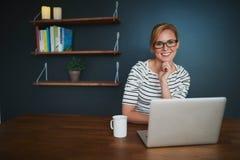 Mujer con el ordenador portátil que sonríe en la cámara Foto de archivo libre de regalías