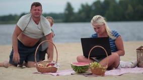 Mujer con el ordenador portátil que trabaja en la playa