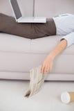Mujer con el ordenador portátil y el papel de las noticias que mienten en el sofá Fotos de archivo