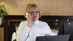 Mujer con el ordenador portátil y el teléfono celular blanco almacen de metraje de vídeo