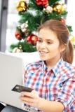 Mujer con el ordenador portátil y la tarjeta de crédito Foto de archivo libre de regalías