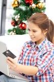 Mujer con el ordenador portátil y la tarjeta de crédito Fotografía de archivo libre de regalías
