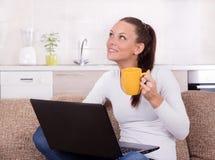 Mujer con el ordenador portátil y la taza de café en el sofá fotos de archivo libres de regalías
