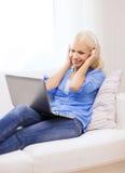 Mujer con el ordenador portátil y los auriculares en casa Fotografía de archivo