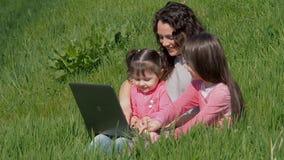 Mujer con el ordenador portátil y los niños en hierba verde Mamá e hijas en el parque La familia está hablando en Skype almacen de metraje de vídeo