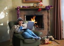 Mujer con el ordenador portátil y los regalos de la Navidad por la chimenea Foto de archivo libre de regalías