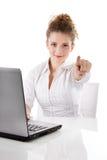 Mujer con el ordenador portátil que señala en usted - a la mujer aislada en blanco detrás Fotos de archivo libres de regalías