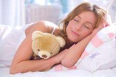 Mujer con el oso de peluche en cama Foto de archivo libre de regalías