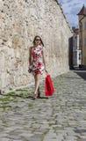 Mujer con el panier rojo en una ciudad Imágenes de archivo libres de regalías