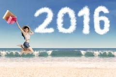 Mujer con el panier y números 2016 en la costa Foto de archivo libre de regalías