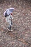 Mujer con el paraguas en lugar de los adoquines en la ciudad Foto de archivo