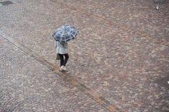 Mujer con el paraguas en lugar de los adoquines en la ciudad Imágenes de archivo libres de regalías
