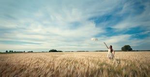 Mujer con el paraguas que recorre en campo. Imagen de archivo