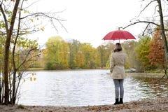 Mujer con el paraguas que se coloca en el lago Imágenes de archivo libres de regalías