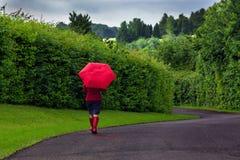 Mujer con el paraguas rojo en un día cubierto. Imagen de archivo libre de regalías