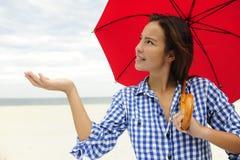 Mujer con el paraguas rojo que toca la lluvia Imagen de archivo