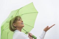 Mujer con el paraguas verde que goza de la lluvia contra el cielo claro Imagenes de archivo