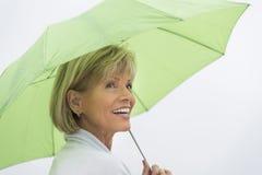 Mujer con el paraguas verde que mira lejos contra el cielo claro foto de archivo