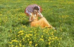 Mujer con el parasol y los dientes de león amarillos Foto de archivo