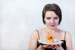 Mujer con el pastel de queso Imagenes de archivo
