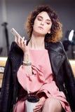 Mujer con el peinado afro que habla en el teléfono durante una sesión fotográfica Imagen de archivo