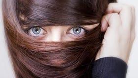 Mujer con el pelo alrededor de los ojos Foto de archivo libre de regalías