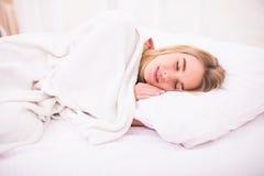 Mujer con el pelo blanco largo que miente y que duerme en cama Foto de archivo libre de regalías