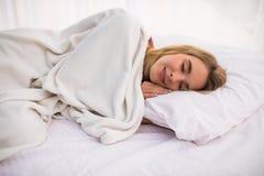 Mujer con el pelo blanco largo que miente y que duerme en cama Fotografía de archivo