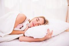 Mujer con el pelo blanco largo que miente y que duerme en cama Fotos de archivo