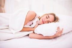 Mujer con el pelo blanco largo que miente y que duerme en cama Foto de archivo