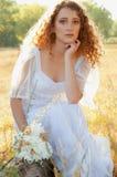 Mujer con el pelo de oro rizado que se sienta en una corteza de árbol en el verano fi Fotografía de archivo