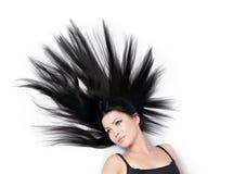 Mujer con el pelo dispersado magnífico en blanco foto de archivo