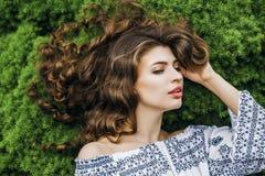 Mujer con el pelo largo que miente en hierba de la primavera fotos de archivo