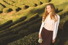 Mujer con el pelo largo con un ramo de flores de snowdrops en el fondo de una plantación de té imágenes de archivo libres de regalías