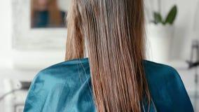 Mujer con el pelo marrón claro recto mojado que se sienta en salón del haircare de la peluquería almacen de metraje de vídeo