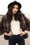 Mujer con el pelo oscuro en ropa elegante y abrigo de pieles lujoso Fotos de archivo libres de regalías